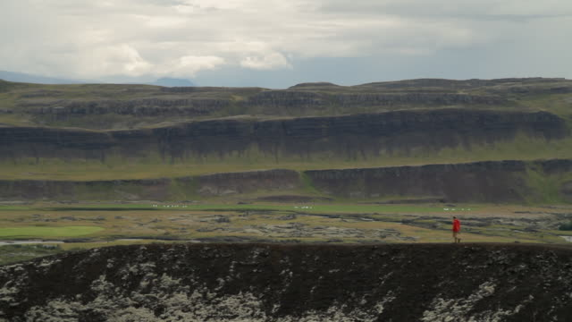 stockvideo's en b-roll-footage met ws view of man walking along mountain ridge with mountainous / reykjavik, hofudhborgarsvaedhi, iceland  - wiese