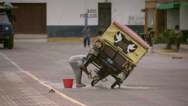 ws view of man washing motorised rickshaw with paintbrush and plastic tub on street / pimentel, lambayeque, peru - risciò video stock e b–roll
