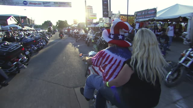 ws pov view of man wearing uncle sam style hat riding on main street with woman in back seat during sturgis motorcycle rally / sturgis, south dakota, united states - uncle sam stock videos & royalty-free footage