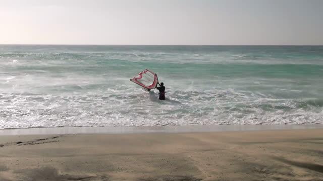 vídeos y material grabado en eventos de stock de ms view of man wind sail surfing and falling in big waves at beach near santa maria / santa maria, sal, cape verde - traje de baño de una pieza