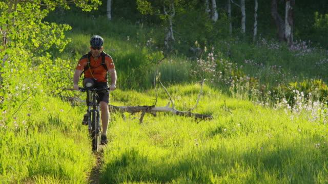 ws td view of man with artificial limb riding mountain bike through grassy hill / american fork canyon, utah, usa - american fork canyon点の映像素材/bロール