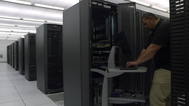 view of man working on computer and woman walking - server room stock videos & royalty-free footage