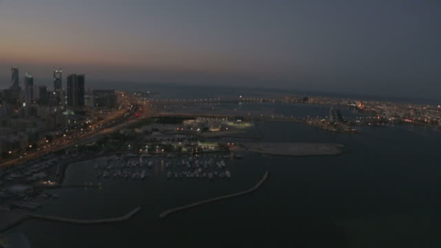 view of manama's cityscape, yacht harbour and the gulf sea at dusk. - urban sprawl stock videos & royalty-free footage
