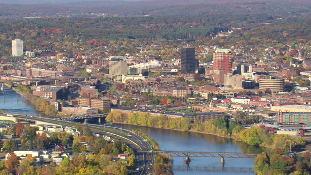 ws aerial zi view of manchester town with autumn color trees / new hampshire, united states - new hampshire stock-videos und b-roll-filmmaterial