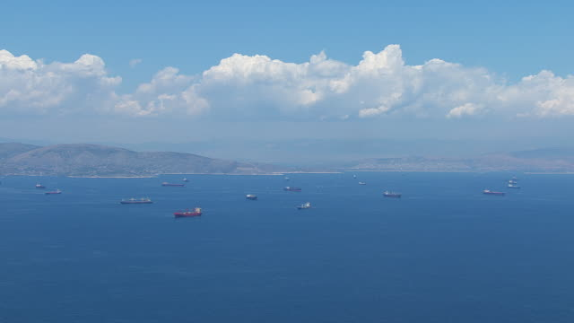 WS AERIAL View of many freighters and sailboats on ocean / Piraeus, Peloponnese, Greece