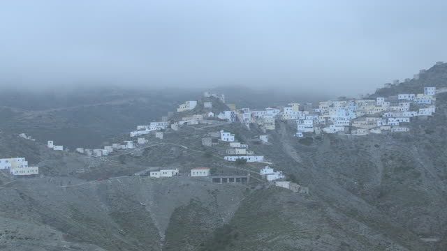 WS AERIAL ZI View of many house on mountain top in fog / Karpathos, Dodecanese, Greece