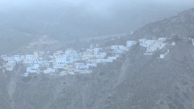 WS AERIAL View of many house on mountain top in fog / Karpathos, Dodecanese, Greece