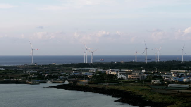 stockvideo's en b-roll-footage met view of many vertical axis wind turbine at wind power station near coastal feature - coastal feature