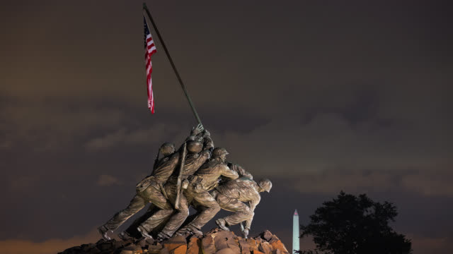 t/l view of marine corps war memorial (iwo jima memorial) at night with washington monument in the background at night / arlington, virginia, usa - monumento ai caduti monumento commemorativo video stock e b–roll