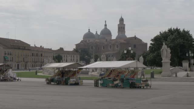 view of market stalls in prato della valle and santa giustina basilica visible in background, padua, veneto, italy, europe - prato stock videos and b-roll footage