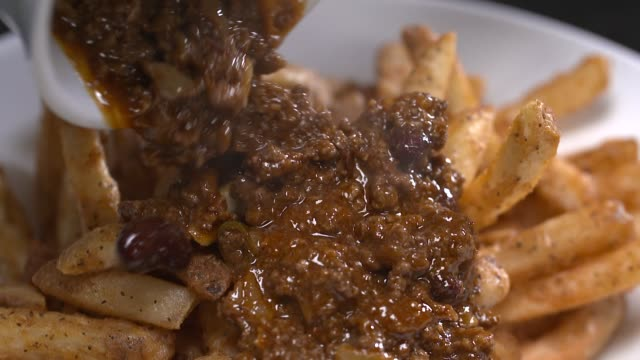 view of meat sauce being poured on french fries - sauce stock videos & royalty-free footage