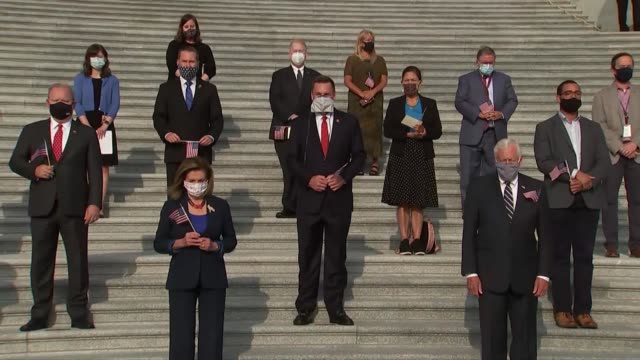 view of members of the house of representatives at base of east front steps of the us capitol building each holding american flags and wearing masks... - minnesmärke bildbanksvideor och videomaterial från bakom kulisserna