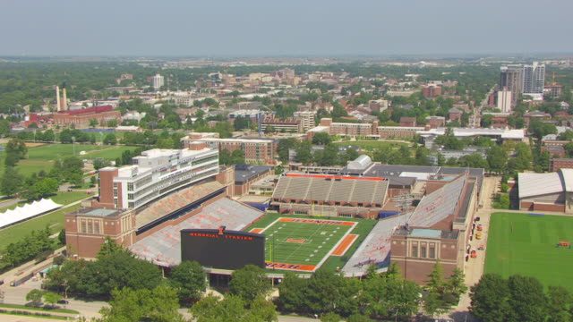 ws aerial pov view of memorial stadium with football pitch, city in background / champaign, illinois, united states - illinois stock videos & royalty-free footage