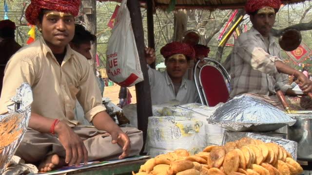 vidéos et rushes de ms zo view of men preparing kachories at surajkund fair / faridabad, haryana, india - assis en tailleur