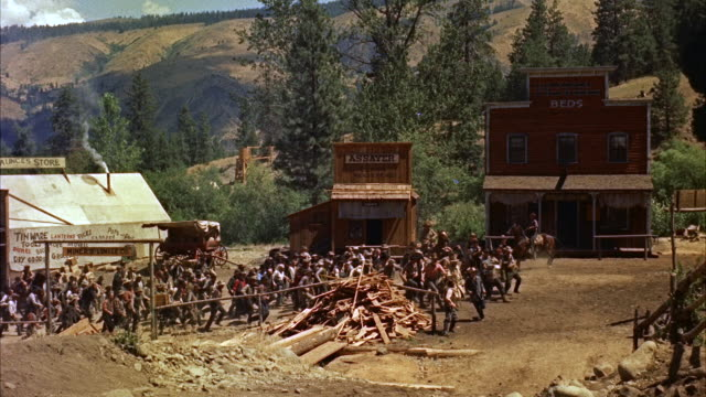 ws pan  view of men rush from saloon and push each other - wild west stock videos & royalty-free footage
