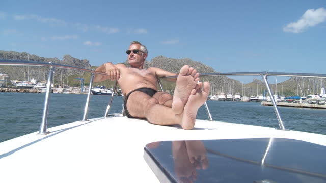 ms view of men seating on bow of speedboat / palma de majorque, majorque, spain - legs crossed at ankle stock videos and b-roll footage