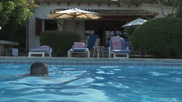 ms cu view of men swimming in swimming pool / palma de majorque, majorque, spain - utebassäng bildbanksvideor och videomaterial från bakom kulisserna