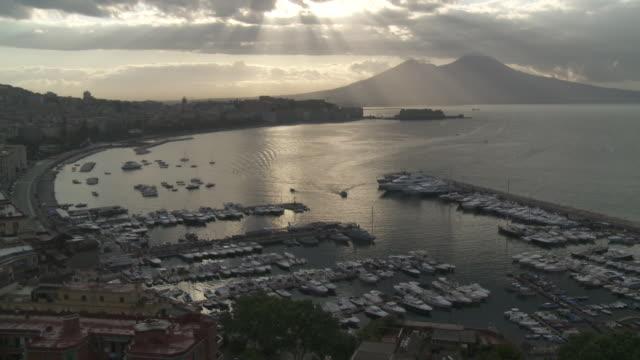 WS View of Mergellina marina in Naples bay at Vesuvius volcano with Dark grey clouds Sunbeam / Naples, Campania, Italy