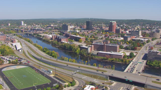 ws aerial pov view of merrimack river near by amoskeag manufacturing company with residential district / manchester, new hampshire, united states - new hampshire stock-videos und b-roll-filmmaterial