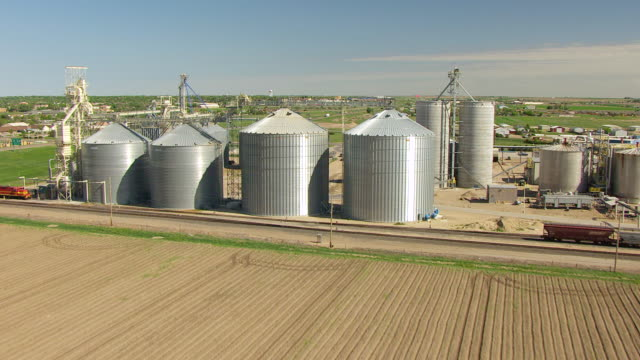 WS AERIAL View of metal silos with cityscape / Garden City, Kansas, United States