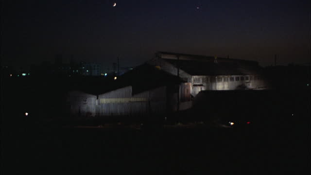 ms view of metal warehouse building at night - industrial district stock videos & royalty-free footage