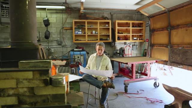 ws view of metal worker looking at blueprints in his shop / santa fe, new mexico, united states - endast en medelålders man bildbanksvideor och videomaterial från bakom kulisserna