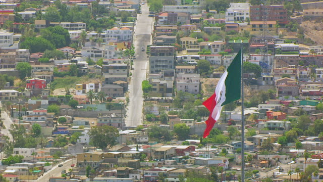 ws aerial pov view of mexican national flag blowing in breeze in tijuana mexico / california, united states - tijuana stock videos & royalty-free footage