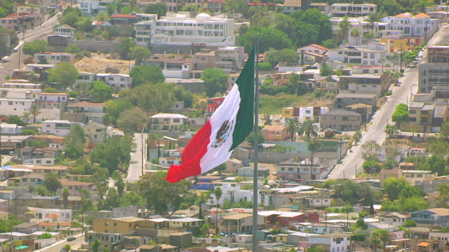ws zo aerial pov view of mexican national flag blowing in breeze in tijuana mexico / california, united states - tijuana stock videos & royalty-free footage