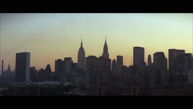 ws view of midtown skyline buildings at dusk / new york city, new york, usa - 1971 stock-videos und b-roll-filmmaterial