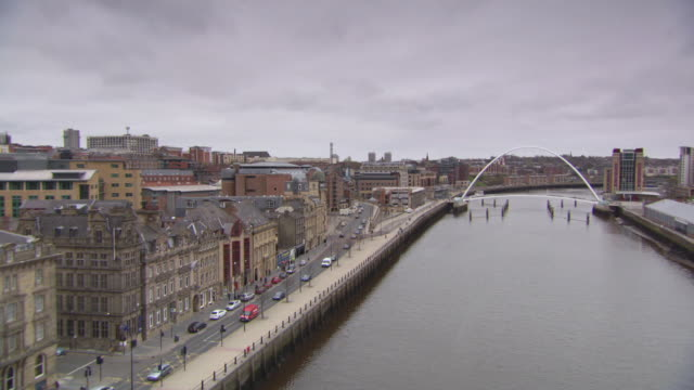 ws pan view of millennium bridge over river in city / newcastle, united kingdom - newcastle upon tyne stock-videos und b-roll-filmmaterial