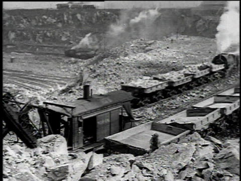 1921 montage view of mining area with train moving slowly through then a steam shovel loading and moving loads of rock and asbestos / asbestos, quebec, canada - アスベスト点の映像素材/bロール