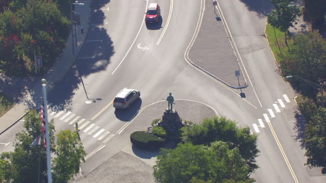 ws aerial pov view of minuteman statue and cars moving on street / lexington, massachusetts, united states - minuteman statue lexington stock videos & royalty-free footage