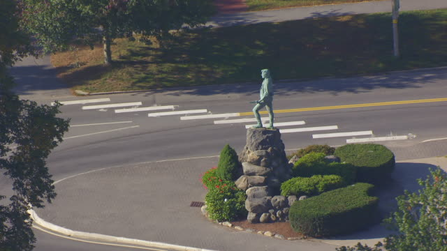 ws aerial pov view of minuteman statue behind trees in town / lexington, massachusetts, united states - minuteman statue lexington stock videos & royalty-free footage