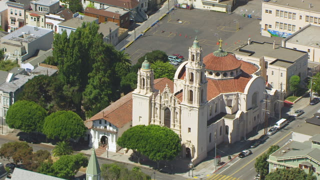 stockvideo's en b-roll-footage met ws zo aerial pov view of mission dolores basilica with cityscape, cars moving on road / san francisco, california, united states - missiehuis