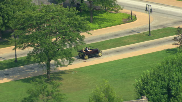 ms aerial ts view of  model t driving down street in greenfield village at henry ford museum / dearborn, michigan, united states - フォード・t型モデル点の映像素材/bロール