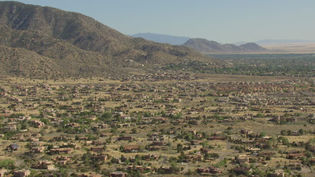 WS AERIAL View of modern adobe style houses with mountains / Albuquerque, New Mexico, United States