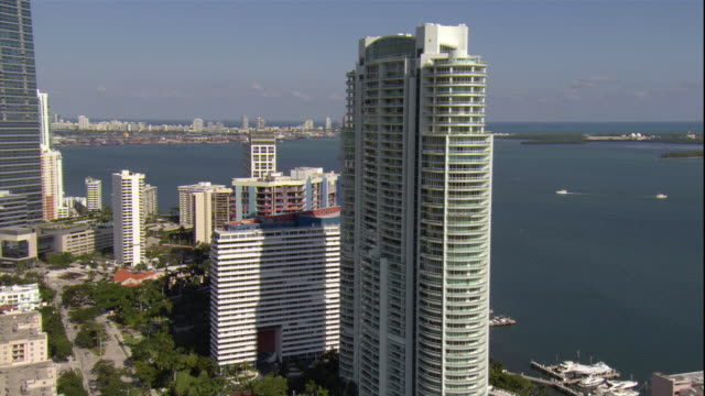 ws pov aerial view of modern condominium skyscraper and other tall buildings close to biscayne bay in downtown miami / miami, florida, usa - biscayne bay stock videos and b-roll footage