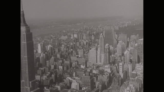 WS AERIAL POV View of modern crowded cityscape, Empire State Building to Rockefeller Center / New York City, New York State, United States