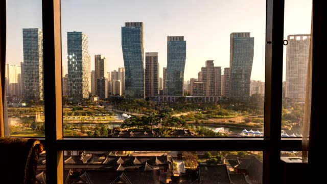 view of modern high-rise building with traditional hotel in songdo central park in sunrise morning - korea stock videos & royalty-free footage