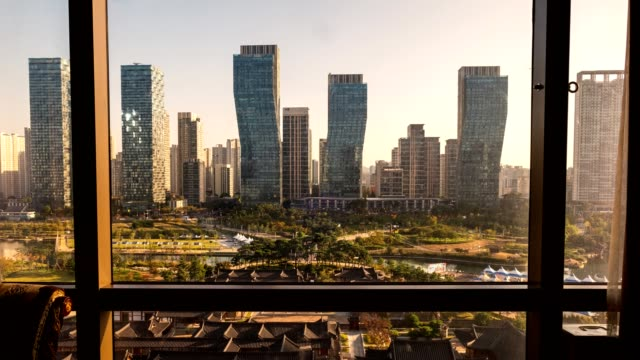 view of modern high-rise building with traditional hotel in songdo central park in sunrise morning - skyscraper stock videos & royalty-free footage