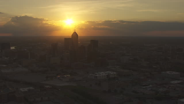 WS AERIAL POV View of modern skyscrapers in downtown Indianapolis during sunset / Indianapolis, Marion County, Indiana, United States