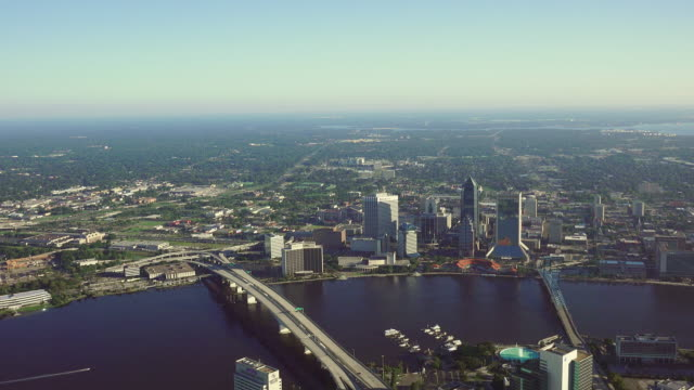 ws aerial pov view of modern skyscrapers in downtown, river in foreground / jacksonville, florida, united states - jacksonville florida video stock e b–roll