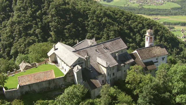 ws aerial ts view of monastery of santa maria assunta above village claro / claro, ticino, switzerland - 女子修道院点の映像素材/bロール