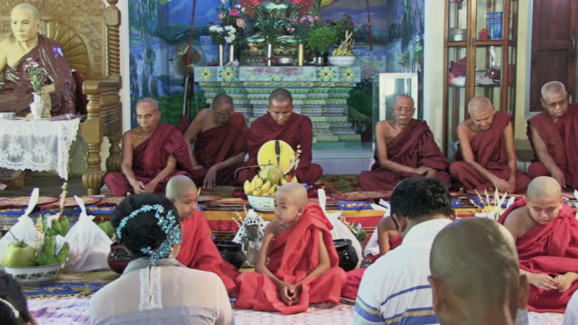 WS View of monks and young monks sitting and praying together, facing other sitting people inside a temple / Bagan, Mandalay Division, Myanmar