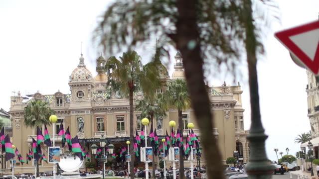 vidéos et rushes de view of monte-carlo casino and mirror sculpture from behind palm tree - jouer aux jeux de hasard