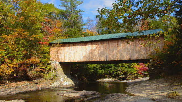 ws view of montgomery covered bridge with fall foliage in northern new england / waterville, vermont, united states - überdachte brücke brücke stock-videos und b-roll-filmmaterial