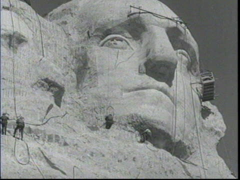 view of monument from the ground / men climbing ropes up to washington's head / borglum hanging from ropes and using a jackhammer near the nose area... - マウントラシュモア国立記念碑点の映像素材/bロール