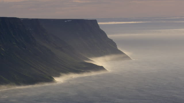 ws areail view of moody cliffs with fog forming / iceland - seascape stock videos & royalty-free footage