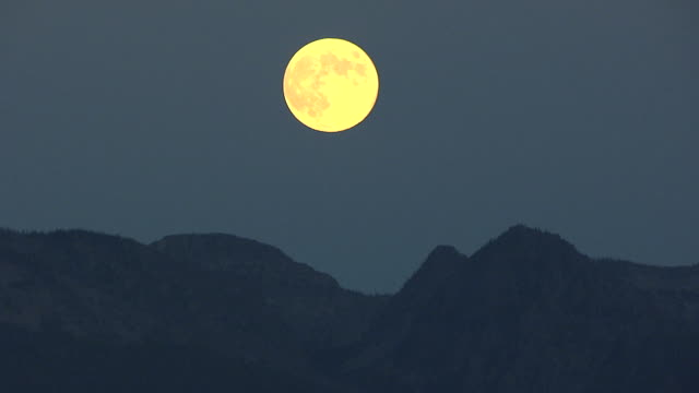 ws aerial zo view of moon in sky with mountains below / montana, united states - real time stock videos & royalty-free footage
