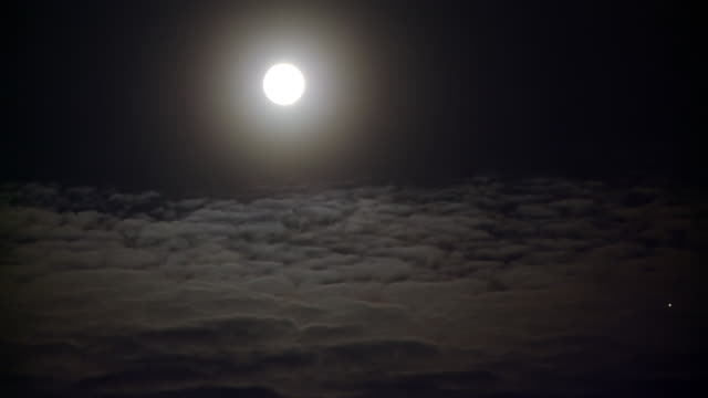 stockvideo's en b-roll-footage met ws t/l view of moon passing from frame with moving clouds / arviat, nunavut, canada - wiese